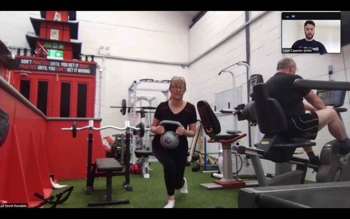 Lady doing front lunge with kettle bell in Gorseinon with personal trainer in Swansea