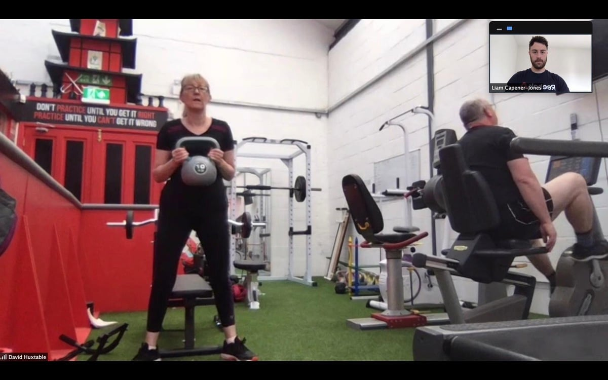 Squat with kettle bell in Gorseinon working with personal trainer online